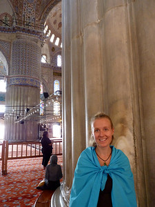 In front of one of the giant pillars in the mosque